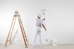 Rear view of painter man looking at blank wall, with paint stick Stock Photography