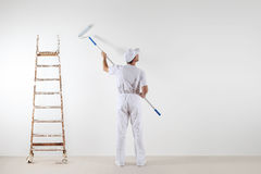 Rear view of painter man looking at blank wall, with paint stick Royalty Free Stock Photography