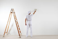 Rear view of painter man looking and painting blank wall, with p. Aint brush and wooden ladder,  on white big space Royalty Free Stock Photography