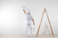 Rear view of painter man painting the wall, with paint roller an. D bucket,  on big empty space with wooden ladder Stock Photos