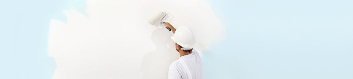 Rear view of painter man painting the wall, with paint roller, i. Rear view of painter man painting the wall, with paint roller,  on big empty space, web banner Royalty Free Stock Photography