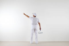 Rear view of painter man pointing with finger the blank wall, wi. Th paint roller, isolated on white room Royalty Free Stock Photo