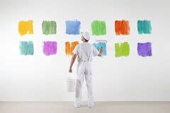 Rear view of painter man who make and chooses from various colors stock images