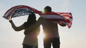 Rear view patriotic family with a large flag of America. In hands outdoors against the rising sun. Flag is waving in the breeze stock video