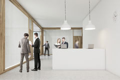 Rear view of people talking and walking near the reception desk Royalty Free Stock Images
