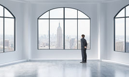 Rear view of a person in formal suit who is looking out the window in a modern loft interior. Stock Photo