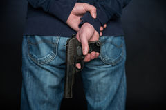 Rear view of the person who holds a hand gun. Royalty Free Stock Photography