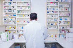 Rear view of a pharmacist working in lab coats. In the pharmacy stock image