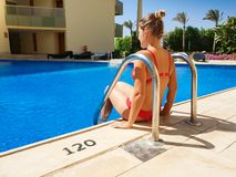Rear view image of beautiful sexy young woman in red bikini sitting on the poolside at hotel resort. Woman relaxing and stock photography