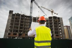 Rear view image of construction engineer checking blueprint of new building under construction. Rear view photo of construction engineer checking blueprint of Stock Images