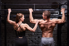 Rear view photo of couple of man and woman in the sportwear making exercise on a horizontal bar against brick wall. Rear view photo of couple of men and women Stock Photo