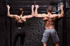 Rear view photo of couple of man and woman in the sportwear making exercise on a horizontal bar against brick wall.