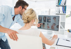 Rear view of photo editors working on computer. In a bright office Royalty Free Stock Images