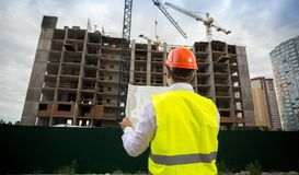 Rear view photo of male architect in hardhat standing on building site and looking on blueprints. Rear view image of male architect in hardhat standing on Stock Photos
