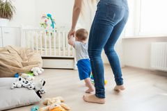 Rear view image of mother holding her baby by hands and teaching making first steps. Rear view photo of mother holding her baby by hands and teaching making royalty free stock image