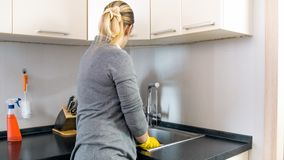 Rear view photo of young housewife standing at kitchen sink. Rear view image of young housewife standing at kitchen sink stock photo