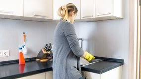 Rear view photo of young housewife washing dishes in kitchen sink. Rear view image of young housewife washing dishes in kitchen sink royalty free stock images