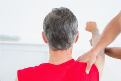 Rear view of a physiotherapist massaging mature mans arm Stock Photos