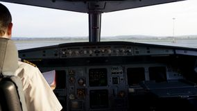 Rear view of pilot operating controls of corporate jet. Captain in the aircraft cockpit, preparing for flight departure Stock Photos