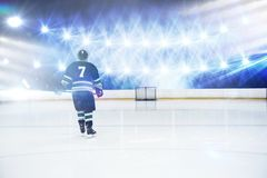 Composite image of rear view of player holding ice hockey stick. Rear view of player holding ice hockey stick against view of strong blue lights royalty free stock photos