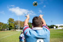 Rear view of player throwing ball while playing rugby at field. On sunny day royalty free stock images