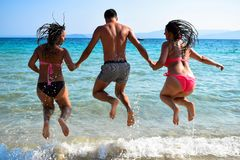Back view of playful people jumping on the beach. stock image