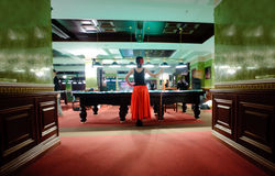Rear view of playing woman. Rear view of woman in billiard club stock photos
