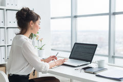 Rear view portrait of a businesswoman sitting on her workplace in the office, typing, looking at pc screen. stock photos