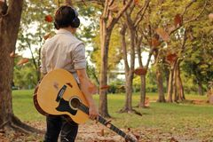 Rear view of portrait of handsome young man holding acoustic guitar with headphones against among falling leaves in the park outdo. Ors Royalty Free Stock Image