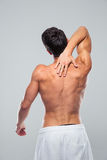 Rear view portrait of a muscular man with neck pain Stock Images