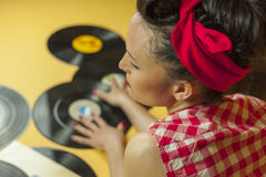 Rear view portrait pin up girl with old vinil records. Selective Stock Photos