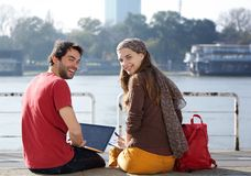 Rear view portrait of two college students smiling. And working on laptop Royalty Free Stock Photo