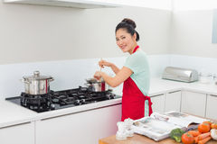 Rear view portrait of a woman preparing food in kitchen Royalty Free Stock Photos