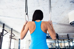 Rear view portrait of woman working out on gimnastic rings Stock Photography