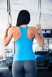 Rear view portrait of woman working out on gimnastic rings Stock Image
