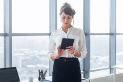 Rear view portrait of a young female office worker using apps at her tablet computer, wearing formal suit, standing near. Workplace, touching screen Stock Photography