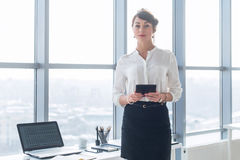 Rear view portrait of a young female office worker using apps at her tablet computer, wearing formal suit, standing near. Workplace, touching screen Royalty Free Stock Images