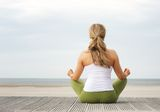Rear view portrait of  young woman sitting at beach in yoga pose Stock Photos