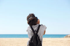 Rear view portrait of young woman sitting by seaside with headphones. Rear view portrait of young woman sitting by seaside listening to music with headphones Stock Images