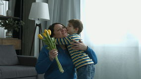 Little boy surprises mother with flowers at home stock footage