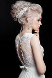 Rear view of pretty bride sensuality posing and turned away, touching chin and face by hand. Blonde woman wearing lace dress, with Royalty Free Stock Images