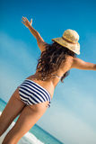 Rear view of pretty brunette looking at the ocean Royalty Free Stock Photos