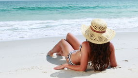 Rear view of pretty brunette looking at the ocean stock video footage
