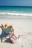 Rear view of pretty brunette relaxing on deck chair at the beach Stock Image