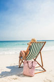 Rear view of pretty brunette relaxing on deck chair at the beach Stock Images