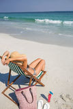 Rear view of pretty brunette relaxing on deck chair at the beach Royalty Free Stock Photo