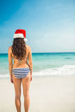 Rear view of pretty brunette in santa hat at the beach Royalty Free Stock Photo