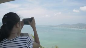 Rear view of pretty girl holding mobile phone while taking picture on view point tower with beautiful scenery of the bay. Rear view of pretty girl holding stock video