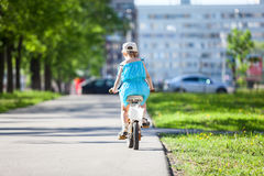 Rear view of pretty girl riding bicycle in park royalty free stock images