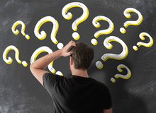 Rear view of puzzled man in t-shirt scratching his head in confusion. Against blackboard filled with question marks vector illustration